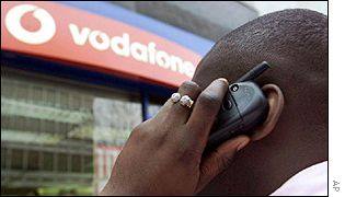 Man using a mobile phone outside a Vodafone store