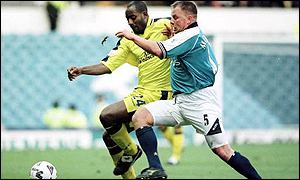 Dele Adebola (left) and Andy Morrison in action at Maine Road