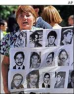 Protester holds banner with photos of the disappeared