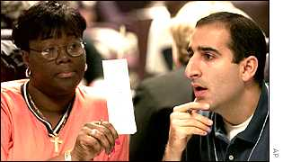 An unidentified county worker, left, shows a Republican observer a ballot at the manual vote recount