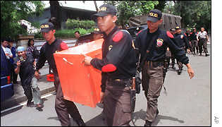 A special police task force carries a box of unidentified equipment to the house of Tommy Suharto on 15/1/01