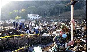 A soldier digs for bodies in Santa Tecla