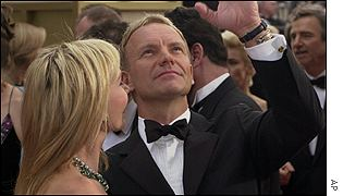 Sting and wife Trudie Styler wave to the fans outside the Golden Globes