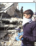A volunteer helper wearing a face-mask surveys the rubble