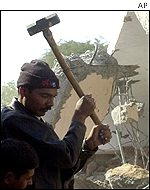 A volunteer uses a sledgehammer to break up debris