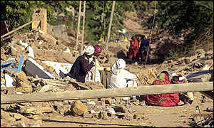 Families sit among the remains of their homes