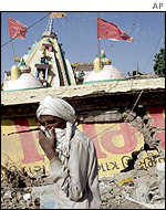 A man covers his face to guard against the stench in Bhachau