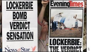 Newspaper front pages go up in a Lockerbie shop