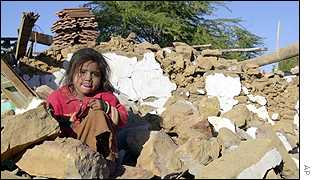 Girl from Rapar village sit on the ruins of her home