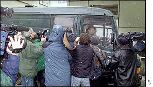 Journalists throng around a police car at the entrance of a court building in Frankfurt