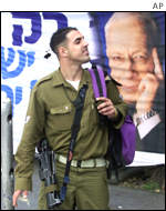 A soldier stands in front of an Ariel Sharon poster