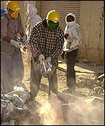 Aid workers spray a decomposed body with disinfectant