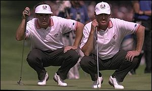 Padraig Harrington and Miguel Jimenez study a putt