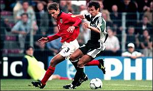 England's Phil Neville is chased by Mehmet Scholl