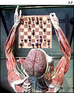 A preserved human corpse sits in front of a chess board