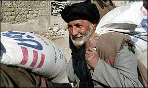 Afghan man carrying sack of wheat