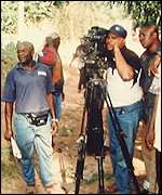 Fred Amata checking a camera during a shoot