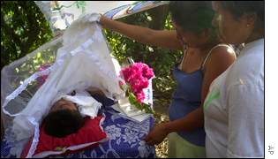 Salvadoran woman lifts lace covering her dead nephew's body