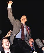 A triumphant William McCrea is carried aloft by supporters
