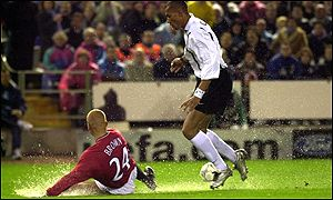 Wes Brown makes a timely intervention at the feet of John Carew