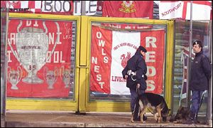 Police stand guard beside Liverpool flags