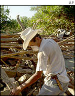 Man at the rubble of his house