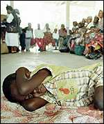 Child waits to be tested for malaria in Mozambique AP