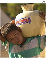 A boy carries a water container