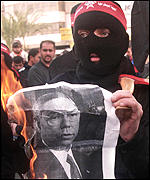 A masked Palestinian protester burns a poster of Colin Powell