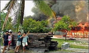 Children play in front of burning abandoned homes