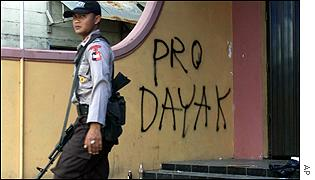 A police officer walks past graffiti declaring a shop Pro Dayak