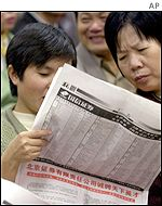 Investors reading local business newspaper