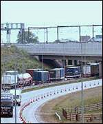 Lorries travel under a rail bridge