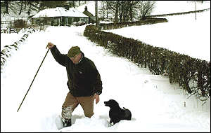 A man attempts to take his dog for a walk in the Scottish borders