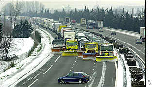 Snow ploughs start to clear a highway near Loriol in central France