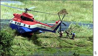 Flood victims make their way to a UN rescue helicopter