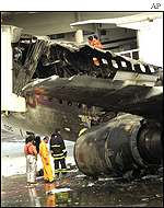 Firefighters look at the burnt plane