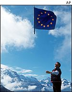 A man swings an European flag in the Swiss alps