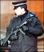 A policeman armed with a sub-machine gun following an IRA bomb