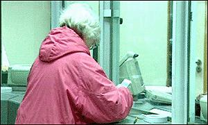 A pensioner collects her pension at the post office