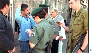 Israeli borderguards check the ID of a Palestinian
