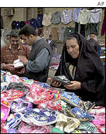 Woman looking at plastic shoes at a market in Baghdad