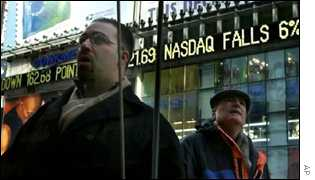 Two men stop to look into the windows of the Nasdaq Marketsite to check current stock figures