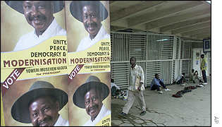 Man walks past Museveni election posters