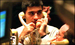 NYSE trader holding two phones