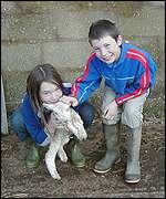 Farmer Adam Quinney's children with newborn lamb