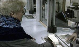 Old woman collecting her pension at the post office