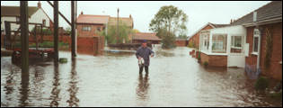 A milkman battles through the floods