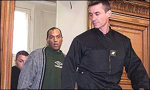 Guy Georges with police officer at the start of his trial