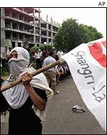 Indonesian hotel workers protest, carrying flags and masking their faces.